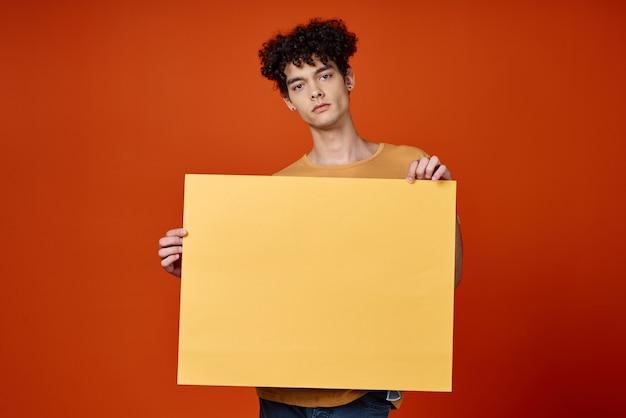 Emocjonalny mężczyzna z kręconymi włosami żółty plakat w rękach. wysokiej jakości zdjęcie