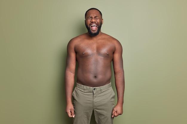 Emocjonalny mężczyzna z nagim tułowiem nosi szorty, krzyczy głośno, szeroko otwiera usta, ma grubą brodę w pozach na tle ściany w kolorze khaki, trzyma ręce opuszczone