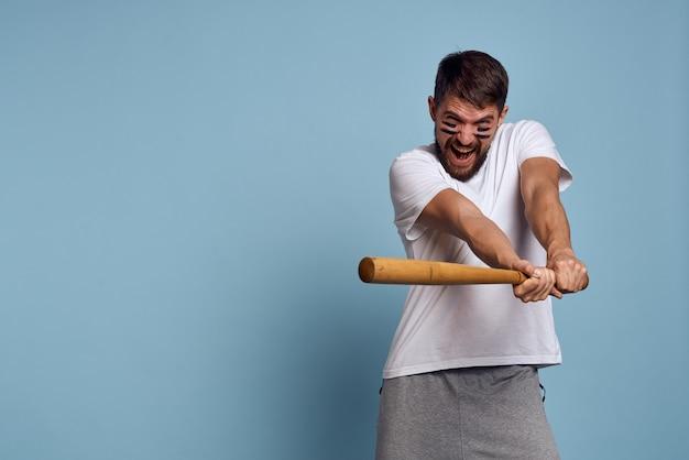 Emocjonalny mężczyzna z nietoperzem w dłoni na niebieskiej przestrzeni i makijażem na twarzy koszulka baseball z czarnymi liniami energetycznymi.