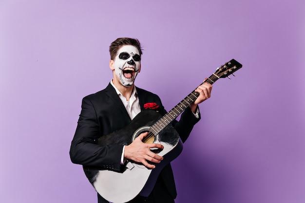 Emocjonalny mężczyzna z pomalowaną meksykańską twarzą głośno śpiewa piosenkę z gitarą na fioletowym tle.