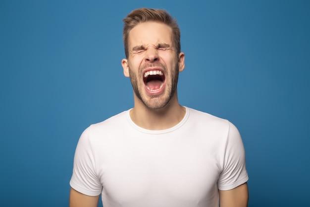 Emocjonalny mężczyzna z zamknięty oczu krzyczeć odizolowywam na błękicie
