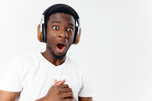 Emocjonalny mężczyzna z zaskoczonym wyrazem twarzy w słuchawkach słuchających muzyki