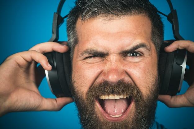 Emocjonalny mężczyzna ze słuchawkami słucha muzyki zbliżenie portret stylowy szczęśliwy mężczyzna słucha muzyki