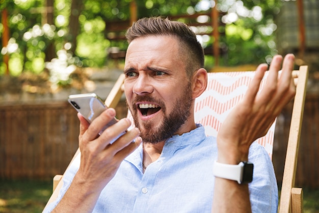 Emocjonalny młody brodaty mężczyzna na zewnątrz rozmawia przez telefon.