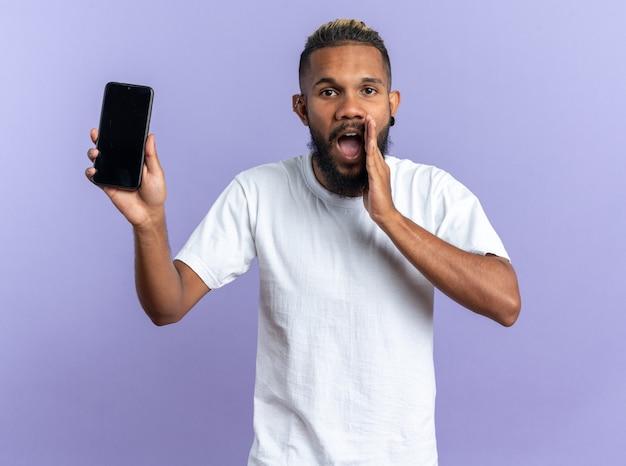 Emocjonalny młody człowiek afroamerykanów w białej koszulce pokazujący smartfona krzyczącego ręką nad ustami stojącego na niebieskim tle