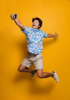 Emocjonalny młody człowiek azjatycki skaczący na białym tle nad żółtą przestrzenią weź selfie przez telefon komórkowy.