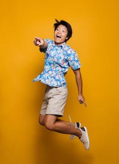 Emocjonalny młody człowiek azjatyckich skoki na białym tle nad wskazując żółtą przestrzeń.