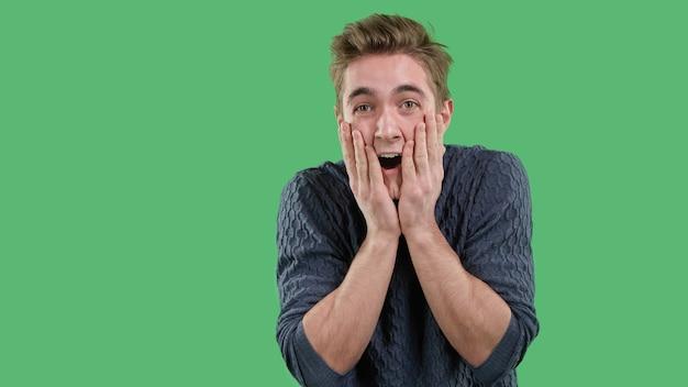 Emocjonalny młody człowiek doświadczający szczęśliwego, radosnego szoku na zielonym, odizolowanym tle