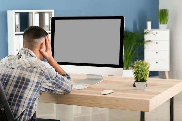 Emocjonalny młody człowiek po popełnieniu błędu podczas pracy z komputerem