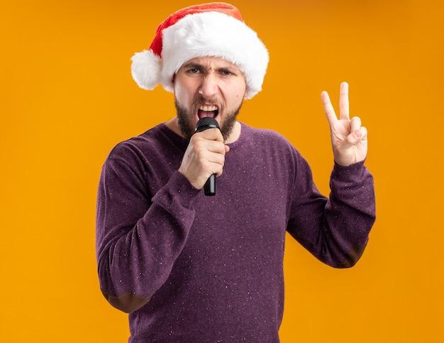 Emocjonalny młody człowiek w fioletowym swetrze i kapeluszu świętego mikołaja, trzymając mikrofon pokazujący śpiew v-znak stojący na pomarańczowym tle