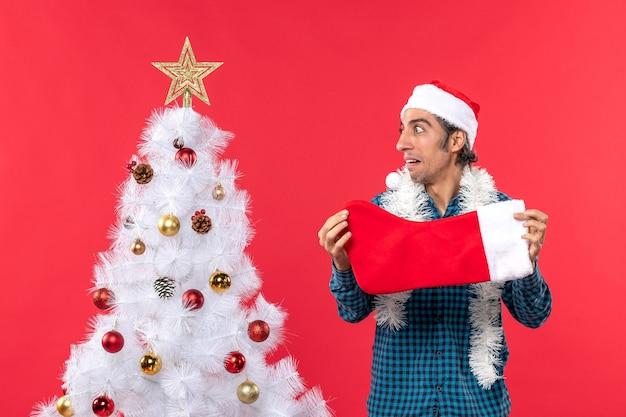 Emocjonalny młody człowiek w kapeluszu świętego mikołaja w niebieskiej koszuli w paski i trzymający świąteczną skarpetę