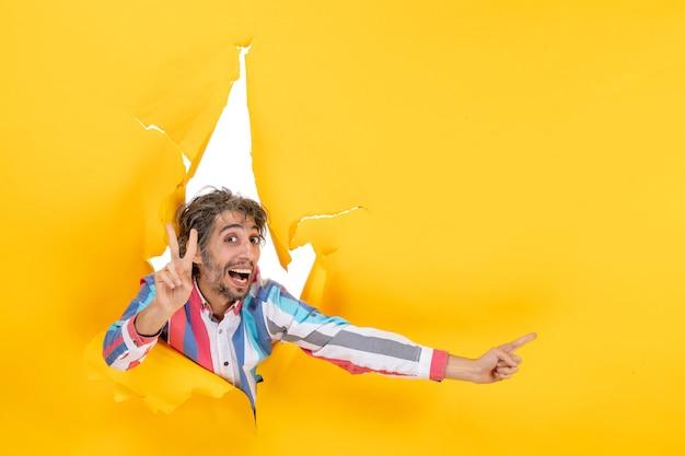 Emocjonalny młody człowiek wskazujący coś na lewą stronę i pokazujący dwa w podartym żółtym tle dziury w papierze