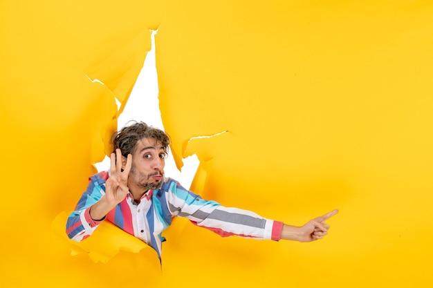 Emocjonalny młody człowiek wskazujący coś na lewą stronę i pokazujący trzy w podartym żółtym tle dziury w papierze