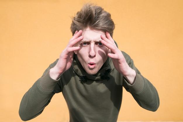Emocjonalny młody człowiek z zaskoczeniem położył ręce na głowie na pomarańczowej ścianie.
