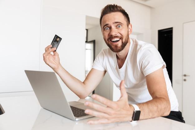Emocjonalny młody człowiek za pomocą komputera przenośnego, trzymając kartę kredytową