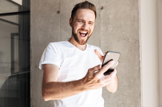 Emocjonalny młody człowiek za pomocą telefonu komórkowego w domu w domu.