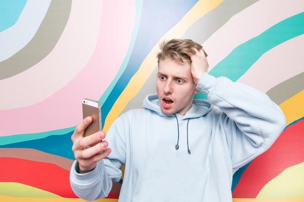 Emocjonalny młody człowiek ze zdumionym wyrazem patrzy na smartfona.