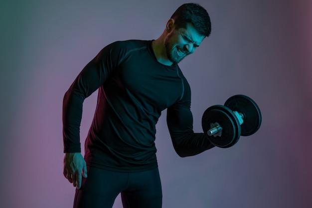 Emocjonalny młody kulturysta wykonujący ćwiczenia bicepsa z hantlami