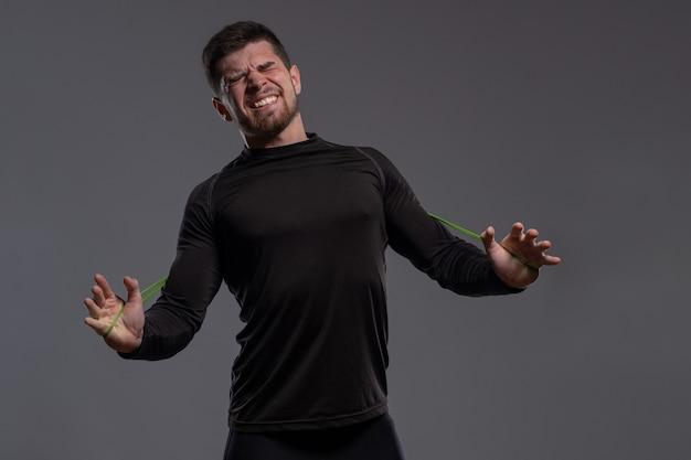 Emocjonalny młody sportowiec rozciągający taśmę oporową rękami