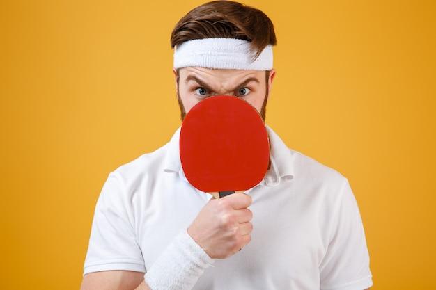 Emocjonalny młody sportowiec trzyma rakietę do tenisa obejmującego usta.