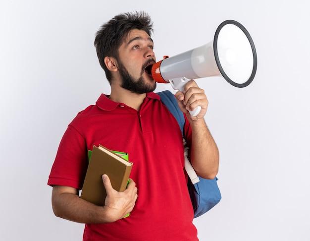 Emocjonalny młody student brodaty facet w czerwonej koszulce polo z plecakiem trzymającym zeszyty krzyczące do megafonu stojącego nad białą ścianą