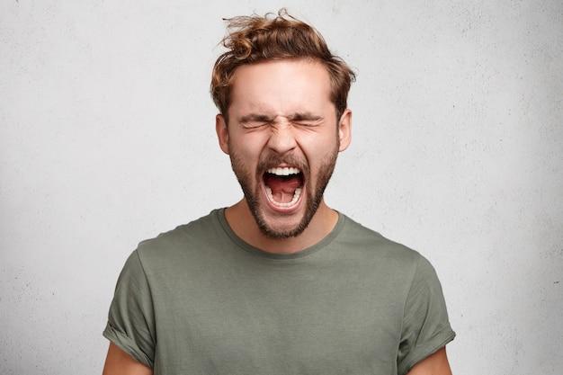 Emocjonalny młodzieniec głośno krzyczy, szeroko otwiera usta, czuje się zdesperowany