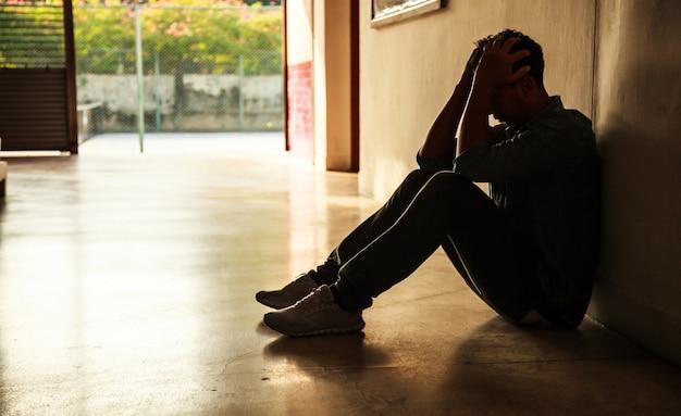 Emocjonalny moment: człowiek siedzi trzymając głowę w ręce, podkreślił, smutny młody mężczyzna o charakterze mentalnym
