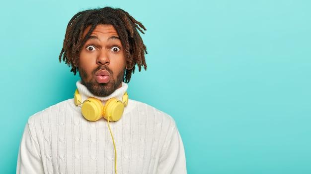 Emocjonalny nastolatek ma wytrzeszczone oczy, nosi żółte słuchawki na szyi, niewiarygodnie patrzy w kamerę, nosi ciepły zimowy sweter