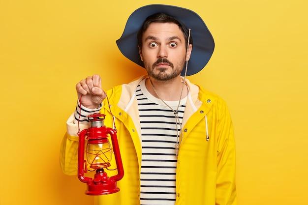 Emocjonalny nieogolony facet nosi kapelusz, sweter w paski i płaszcz przeciwdeszczowy, trzyma lampę naftową, spędza weekend na łonie natury, lubi nocny postój