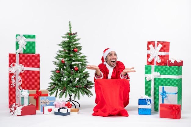 Emocjonalny podekscytowany młody człowiek przebrany za świętego mikołaja z prezentami i ozdobioną choinką reaguje radośnie na białym tle