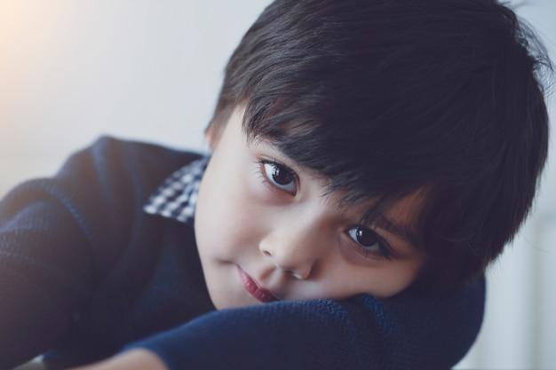 Emocjonalny portret caucasian dzieciak z główkowanie twarzą