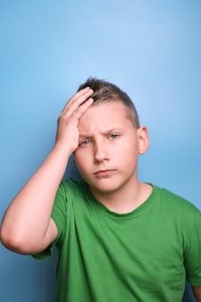 Emocjonalny portret chłopca zakrywający głowę ręką będącą zmęczoną bólem głowy pokazującym prawdziwe emocje