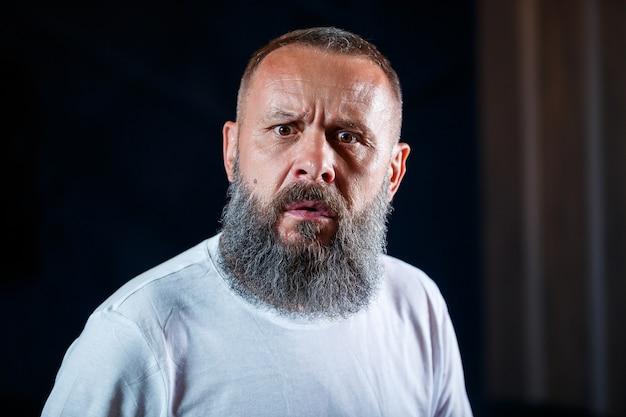 Emocjonalny portret dorosłego siwego mężczyzny z brodą w białej koszulce