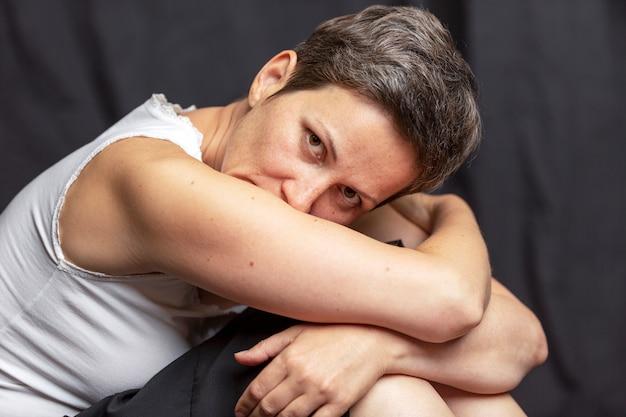 Emocjonalny portret dorosłej kobiety z krótkimi włosami. czarne tło.