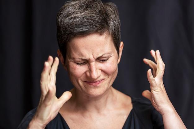 Emocjonalny portret dorosłej kobiety z krótkimi włosami i zamkniętymi oczami. czarne tło.
