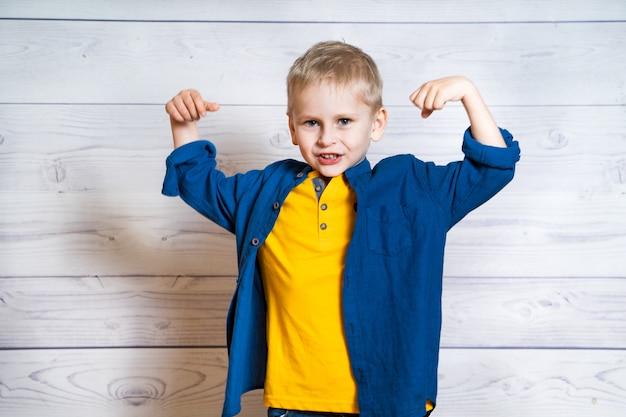Emocjonalny portret małego blond chłopca na sobie niebieską koszulę. śliczny dzieciak pokazuje siłę jego rękami podczas gdy patrzejący