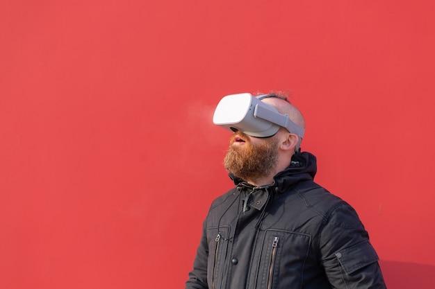 Emocjonalny portret mężczyzny na ulicy w okularach rzeczywistości na tle czerwonej ściany