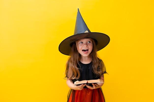 Emocjonalny portret wesołej dziewczynki w kostiumie wiedźmy na halloween