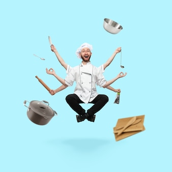 Emocjonalny przystojny kuchenka, szef kuchni wieloręki piekarz lewitujący na białym tle na niebieskim tle studio z wyposażeniem. pojęcie zawodu, pracy, pracy, gotowania, kuchni. wielozadaniowość jak shiva.