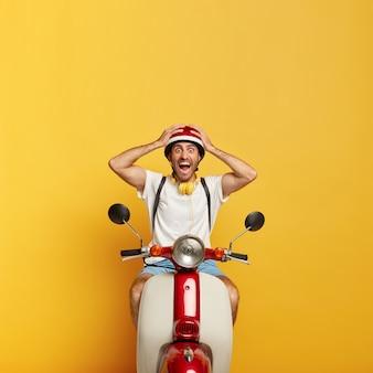 Emocjonalny przystojny mężczyzna kierowca na skuterze z czerwonym kaskiem