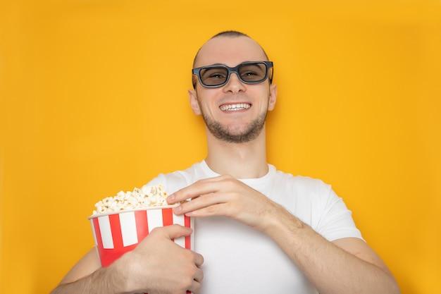 Emocjonalny przystojny w okularach 3d oglądający film z popcornem.