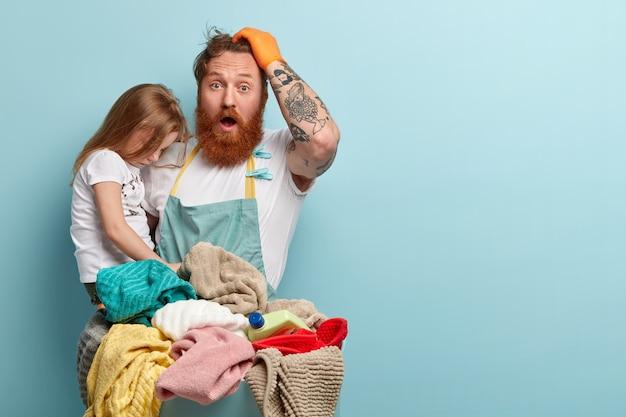Emocjonalny rudowłosy facet trzyma rękę na głowie, szeroko otwiera usta, zszokowany, że ma dużo pracy nad domem