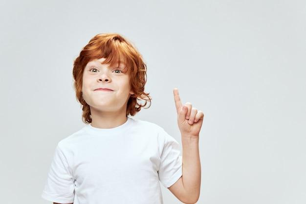 Emocjonalny rudy chłopak pokazuje kciuk w białej koszulce