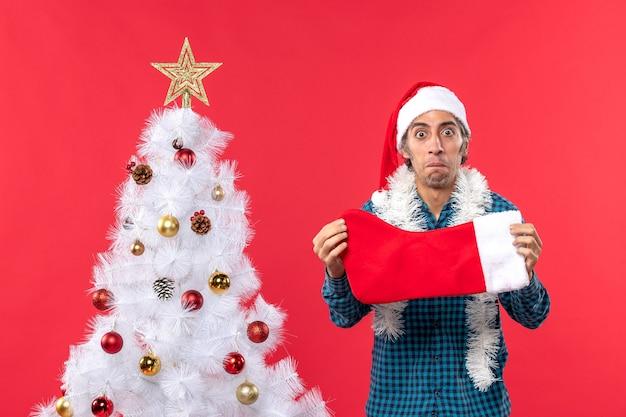 Emocjonalny smutny młody człowiek z czapką świętego mikołaja w niebieskiej koszuli w paski i trzyma świąteczną skarpetę