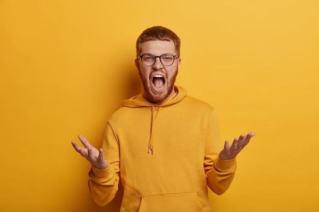 Emocjonalny szalony agresywny hipster podnosi dłonie i wrzeszczy ze złością, ma gęstą rudą brodę i rude włosy, czeka na wyjaśnienia, nosi bluzę z kapturem, odizolowaną na żółtej ścianie. negatywne emocje
