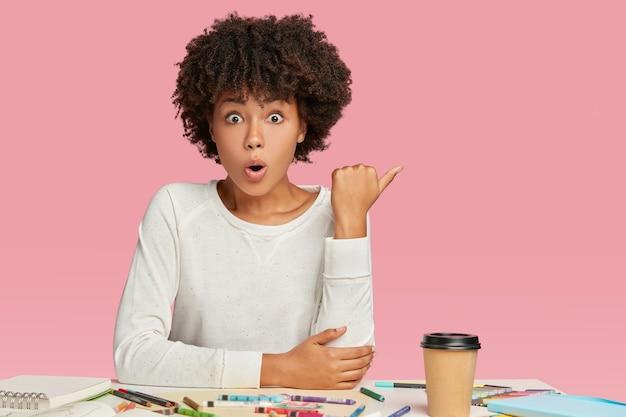 Emocjonalny uczeń o wyłupiastych oczach ma ciemną skórę i fryzurę w stylu afro, wskazuje kciuk w bok