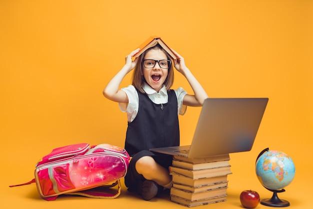 Emocjonalny uczeń siedzi za stosem książek, a laptop trzyma książkę na głowie koncepcja edukacji dzieci