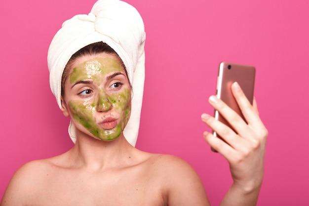 Emocjonalny uroczy kosmetolog robi selfie na portalach społecznościowych