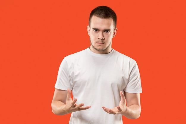 Emocjonalny zły człowiek na tle studio. emocjonalna, młoda twarz. portret mężczyzny w połowie długości.