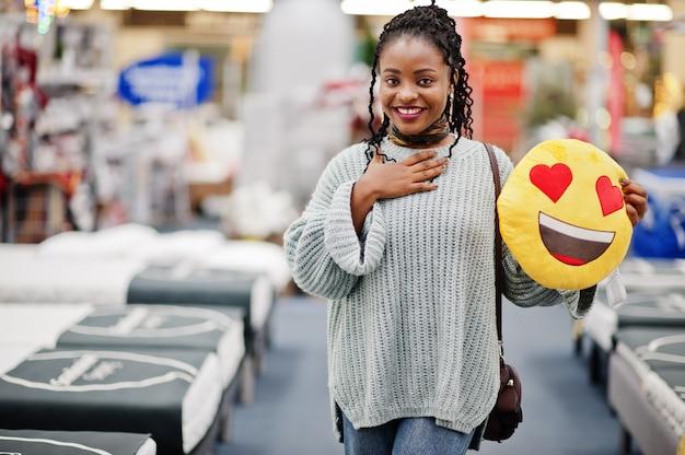 Emoji twarzy miłości serca. afrykańska kobieta z poduszką w nowożytnym domu wyposażenia sklepie.